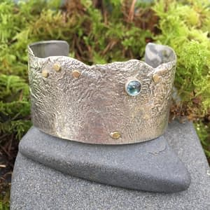 reticulated silver cuff with precious gemstone