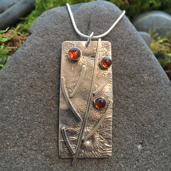 branching out pendant with red gemstones